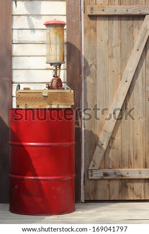The drum of fuel and hand pump in old gasoline station - stock photo