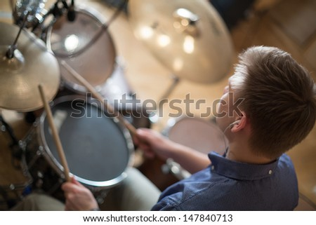 The drummer with headphones plays the drum kit in the studio - stock photo