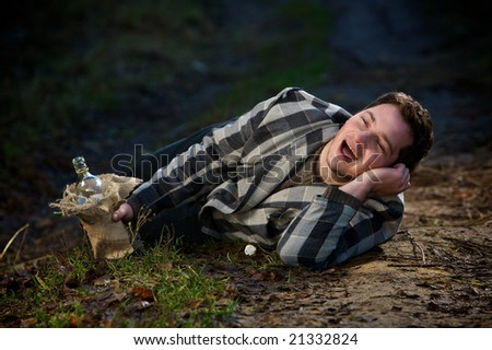 The drunkard lies on road and sings - stock photo