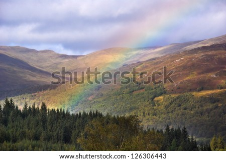The Duke's Pass, Stirling, Scotland, where a colorful rainbow arcs across the Trossachs. Mist rises from the glen, a steep valley enclosed by dark pine forest and heather covered moors and mountains. - stock photo