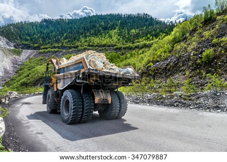 the dump truck carries the stones on the road - stock photo