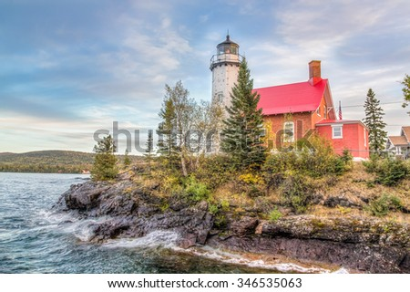 The Eagle Harbor Light, perched on a rocky outcropping, stands on the Lake Superior coast of northwestern Michigan's Keweenaw Peninsula. - stock photo