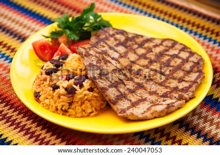 the eal steak with garnish rice with  beans on the yellow plate - stock photo
