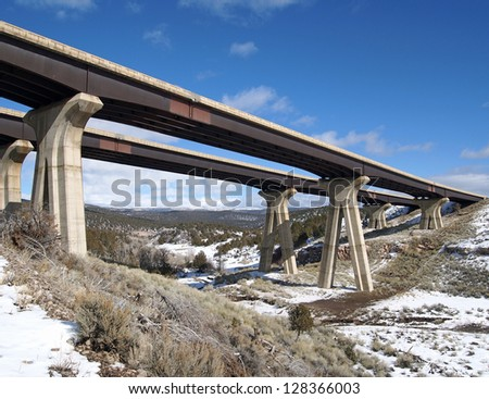 The east and west bound lanes of an interstate cross a canyon. - stock photo