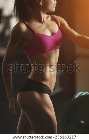 The effect of oil paints. Brunette sexy fitness girl in pink sport wear with perfect body in the gym posing before training set. Part of body - stock photo