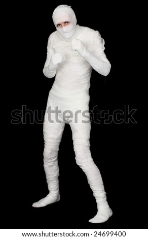 The Egyptian mummy standing on a black background - stock photo