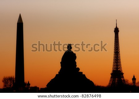 The Eiffel Tower and the Obelisk silhouetted against a fiery sunset - stock photo