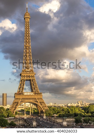 The Eiffel Tower in Paris France glows in evening sunlight with dark clouds over head.  - stock photo