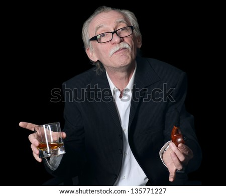 The elderly man with a glass of whisky on a black background - stock photo