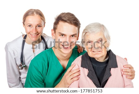 The elderly woman with her helpful caregivers - stock photo
