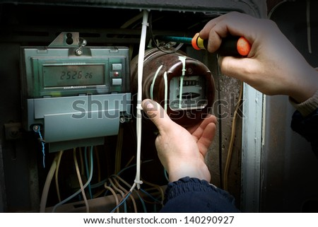 The electrician changes the old electric meter for the new. - stock photo