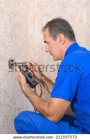 The electrician measuring the voltage at the wall outlet - stock photo