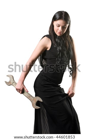The elegant woman in a black dress with a spanner - stock photo