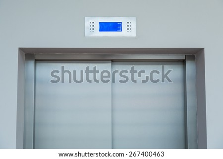 The elevator doors with visible display of floor numbers, interior of the building. - stock photo