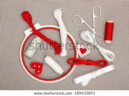 The embroidery hoop, red and white sewing threads, ribbons, beads on canvas background - stock photo