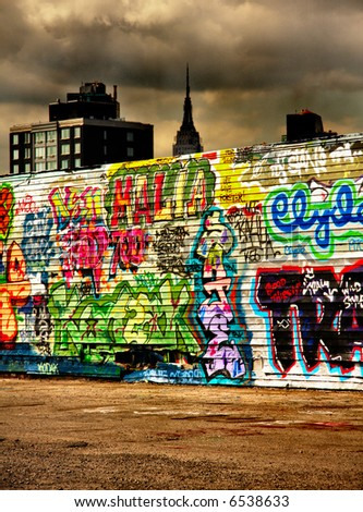 The empire state building in the background towers over a colourful wall of graffiti - stock photo