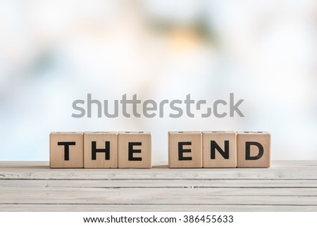 The end sign with wooden blocks on a table - stock photo