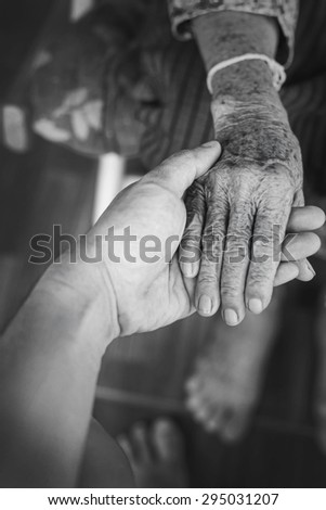 The engagement of young hand touches and holds an old wrinkled hand,monochrome.  - stock photo
