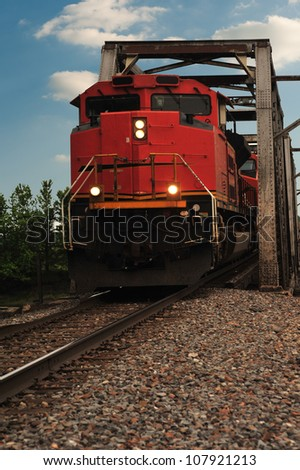 The engine of a freight train emerges from the steel frame of a narrow railroad bridge crossing the river in this close-up shot of the diesel locomotive. - stock photo