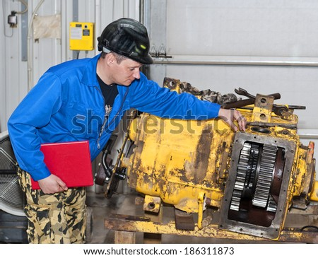 The engineer checks the transmission mechanism. - stock photo