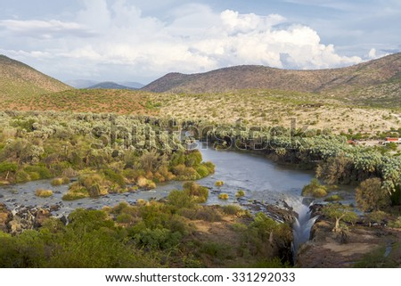The Epupa Falls are created by the Kunene River on the border of Angola and Namibia, in the Kaokoland area of the Kunene Region. - stock photo
