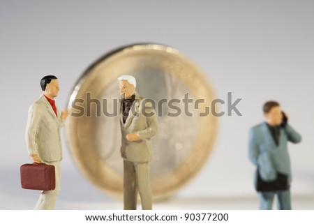 The Euro Crisis, closeup of worried miniature model businessmen in discussion near a Euro coin. - stock photo