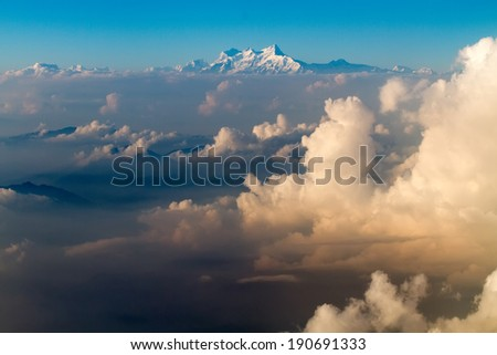 The Everest mount aerial view from plane over cloud sea before landing in Kathmandu in Nepal - stock photo