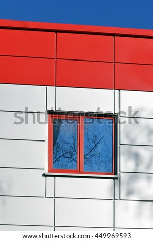 The facade of a modern building of red and white sandwich panels with a window. - stock photo