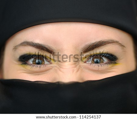 The face of beautiful angry girl in a black yashmak - stock photo