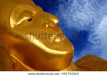 The face of the golden reclining Buddha from the public temple on the blue sky with clouds background. - stock photo