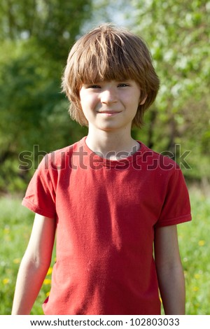 The fair-haired boy in a red T-shirt on sunny day - stock photo
