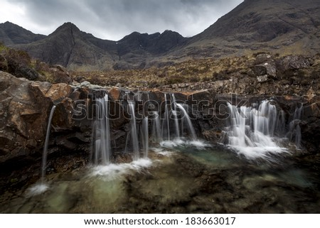 The Fairy Pools on a typical Scottish day. Threatning clouds hanging over the Cuillin range. - stock photo