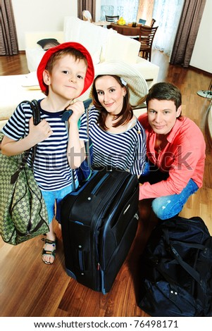 The family at home with a big suitcases. - stock photo