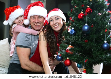 The family dresses up Christmas tree - stock photo
