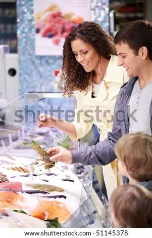The family in shop at seafood chooses meal - stock photo