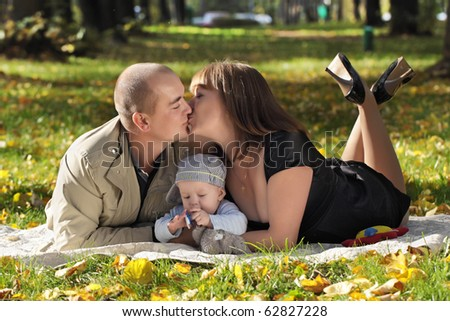 The family lies on a grass in park and kiss - stock photo