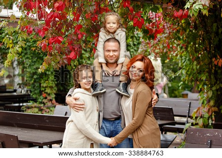 The family - mom, dad and two charming sisters in the same curly beige knit sweater, against the background of red grapes in autumn - stock photo