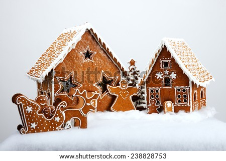 The family near hand-made eatable gingerbread house and New Year Trees with snow decoration - stock photo