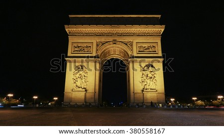 The famous Champs-Elysees arch illuminated with bright lights at night and street in foreground - stock photo
