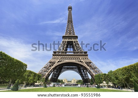 The famous Eiffel Tower in Paris against a dramatic blue sky - stock photo