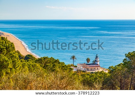 The famous lighthouse near Calella, Spain, overlooking the blue Mediterranean Sea. - stock photo