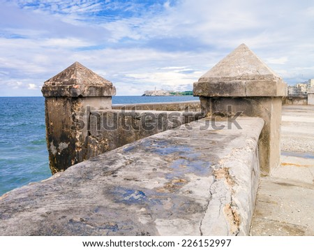 The famous Malecon seawall in Havana with El Morro castle on the background - stock photo