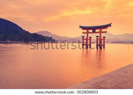 The famous orange floating shinto gate (Torii) of Itsukushima shrine, Miyajima island of Hiroshima prefecture, Japan at sunset. - stock photo