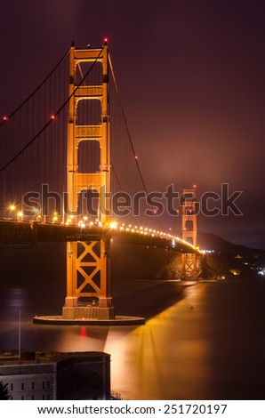 The famous San Francisco Golden Gate Bridge in California, United States of America. A long exposure of Fort Point, the bay and the illuminated red suspended bridge at night looking as if on fire. - stock photo