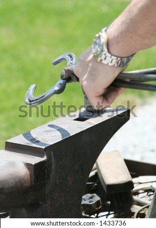 The farrier shapes the heated shoe using a hammer and anvil. Shallow dof. - stock photo