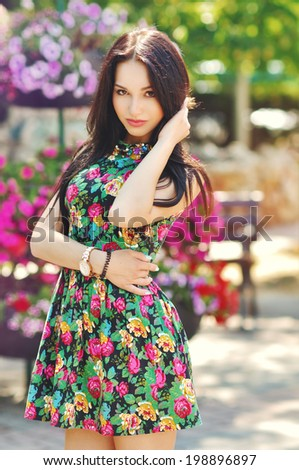 the fashionable beautiful girl walks around the city in a summer dress among flowers in the summer - stock photo
