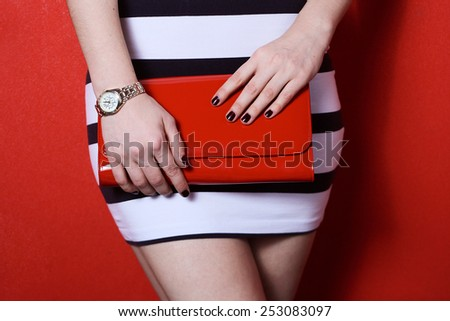 The fashionable young woman in striped skirt holding red handbag clutch .red background  - stock photo
