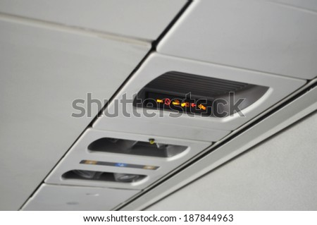 The fasten seatbelt light has come on. Please take your seats. These the are no smoking and seat belt signs on an airplane. - stock photo