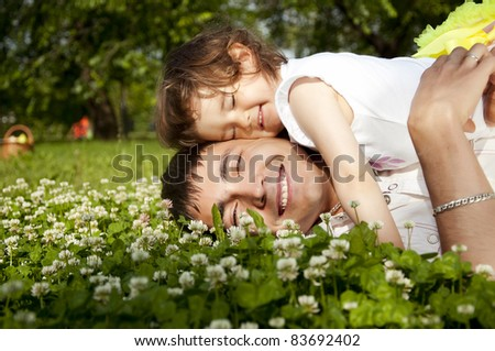 The father and the daughter together lay on a grass - stock photo