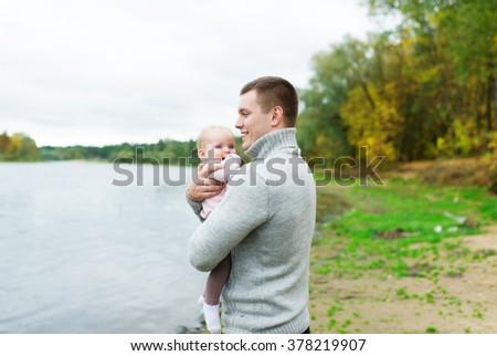 The father holds the little daughter on hands. They are on the river bank during the autumn period. - stock photo